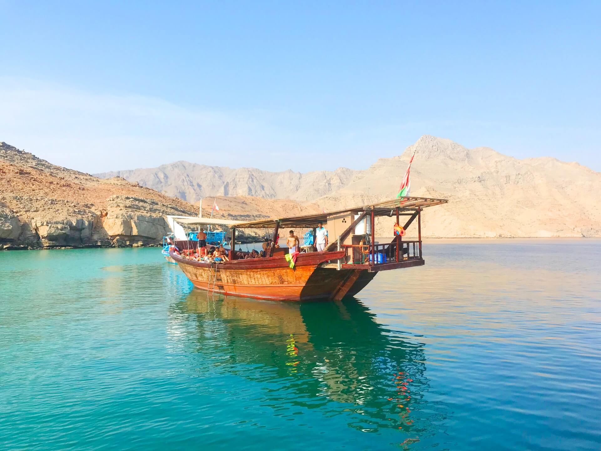 a traditional dhow boat on the blue waters of musandam in oman