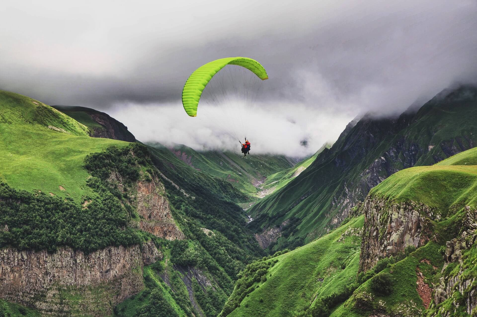 A tourist enjoying a paragliding activity somewhere green in Oman