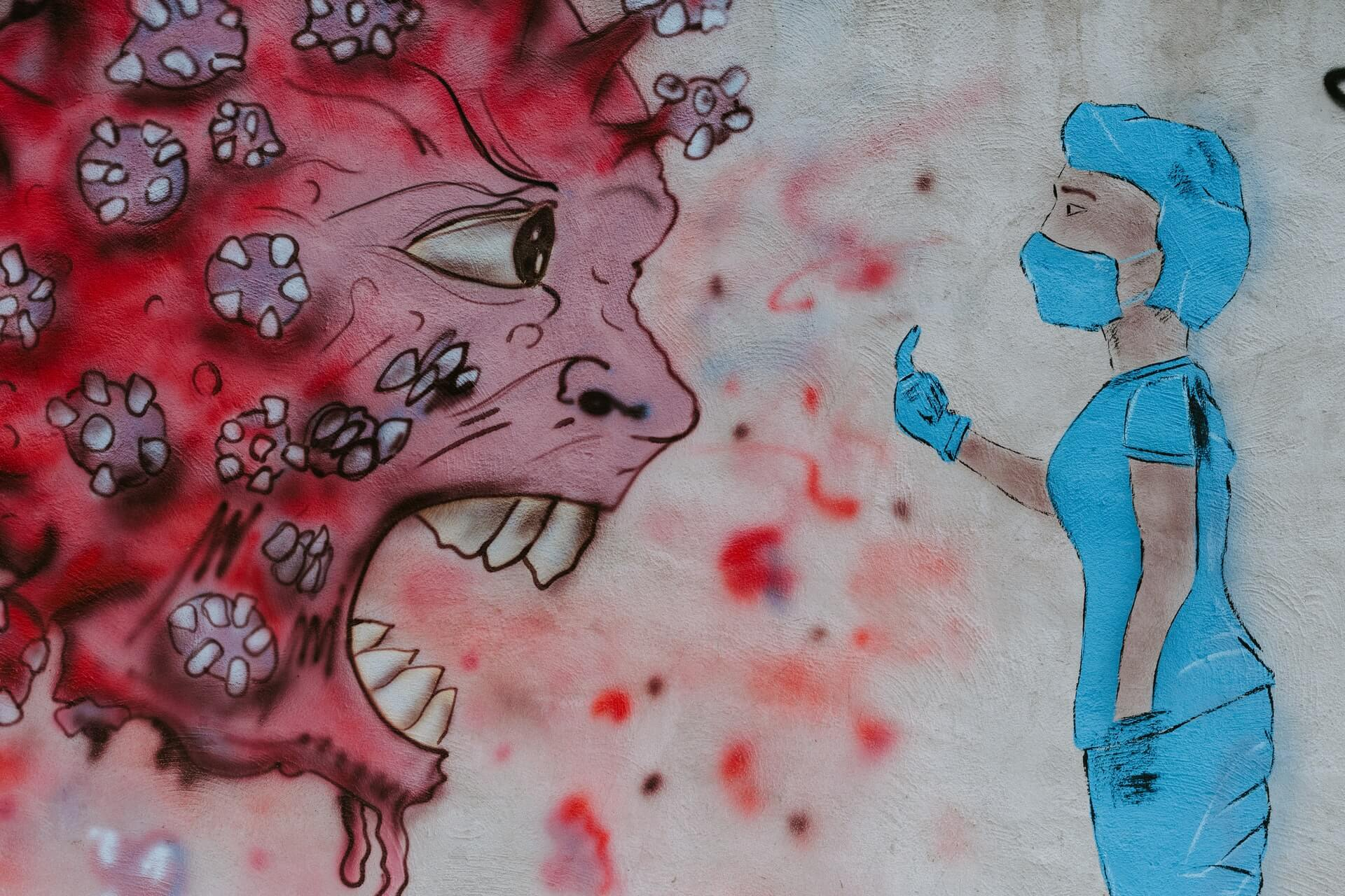 Street art portraying a frontline worker flipping off a COVID virus