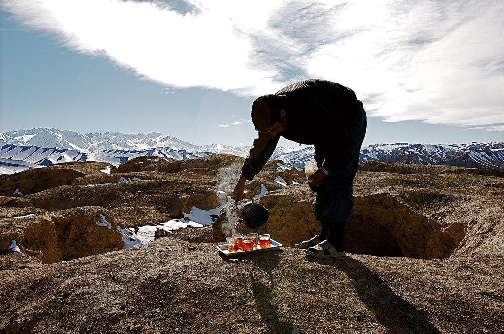 A man pours several cups of tea within snow capped mountains in Afghanistan.