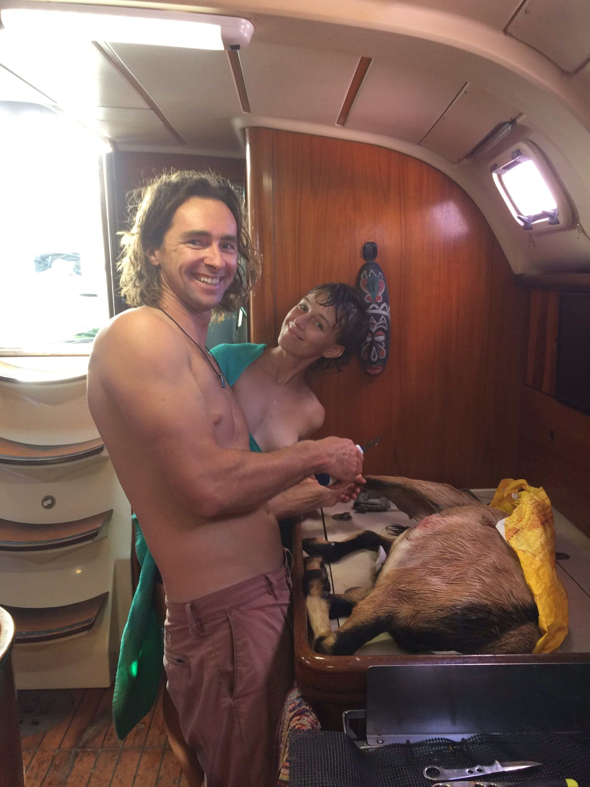 A man and a woman on their liveaboard sailboat. A goat they killed is in front of them.