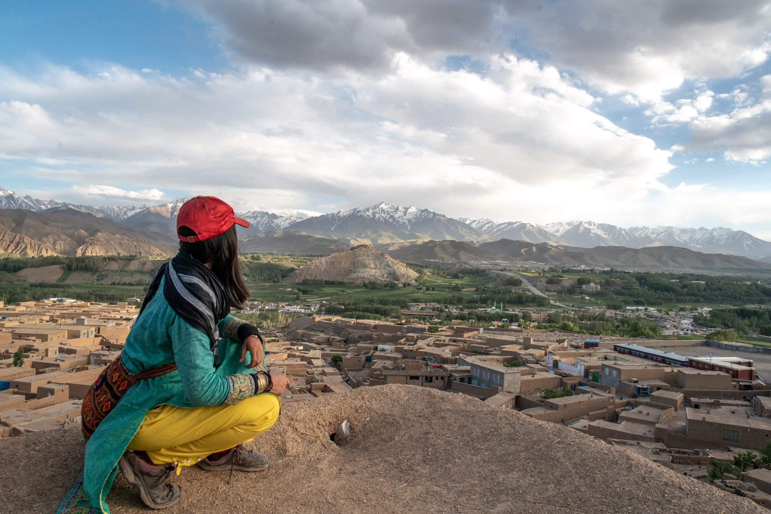 A girl in a red cap crouches and looks at the Bamiyan mountains in Afghanistan.