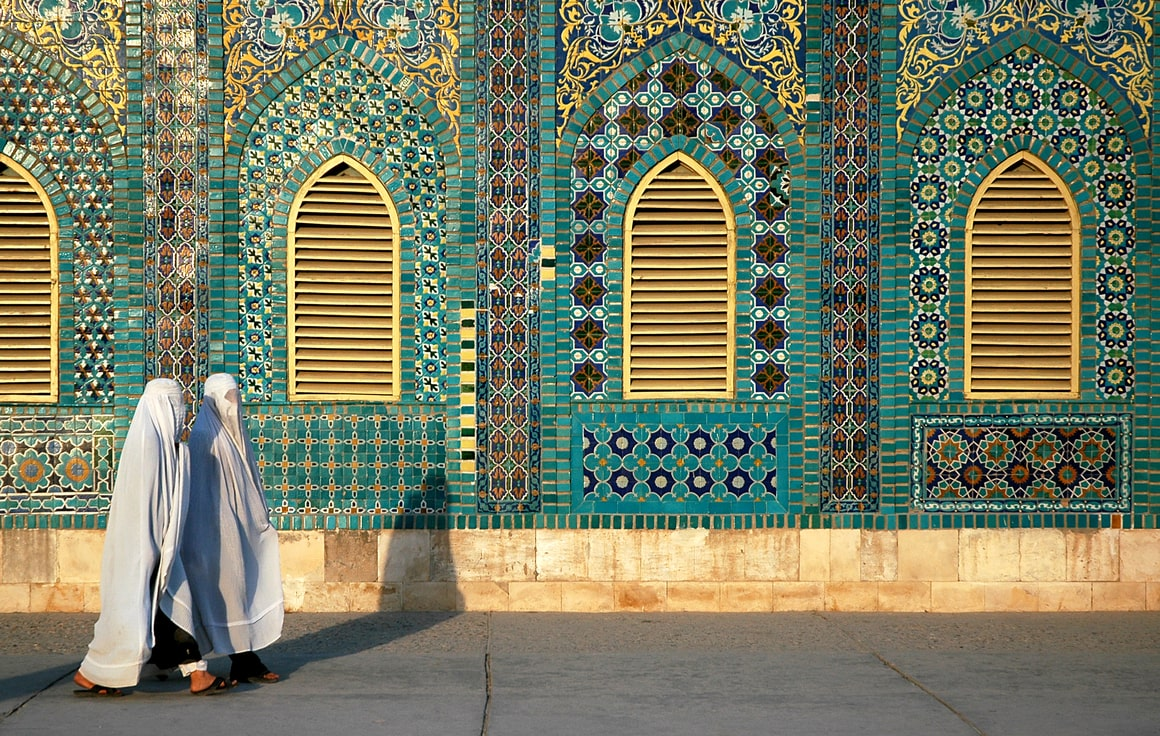 Two women in white hijabs walk past a turquoise tiled mosque.