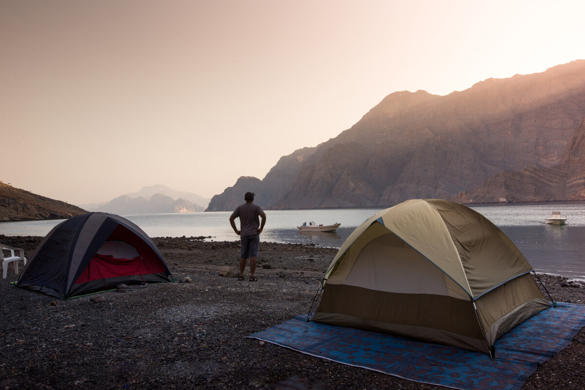man standing in between two tents watching an orange sunset while visiting oman