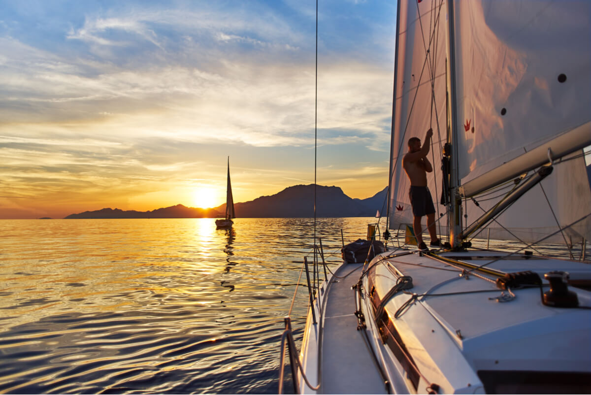 A man stands on his sailboat and raises the mainsail at sunset.