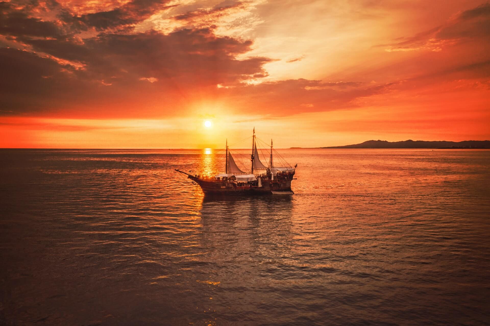 A sailboat mid-cruise on a sunset lake.