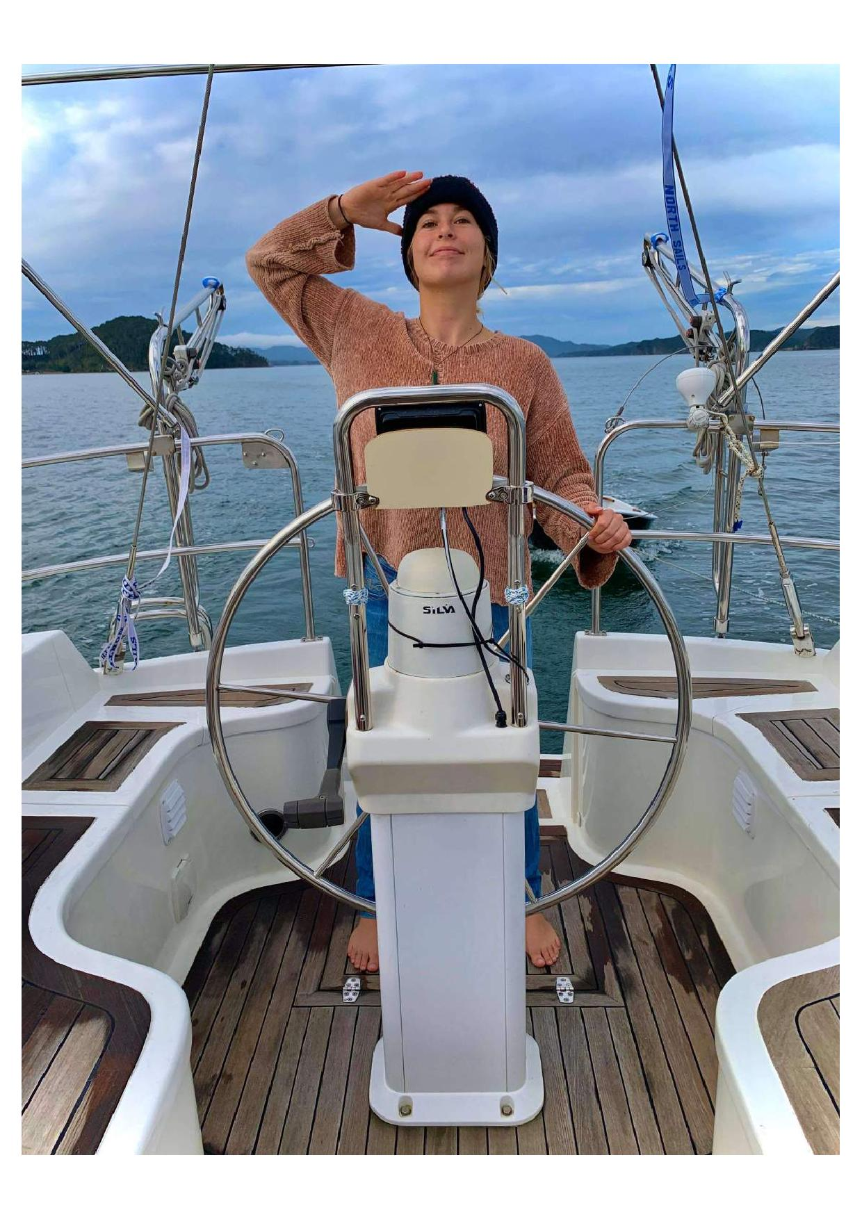 A girl stands at the helm of a sailboat looking at the horizon.