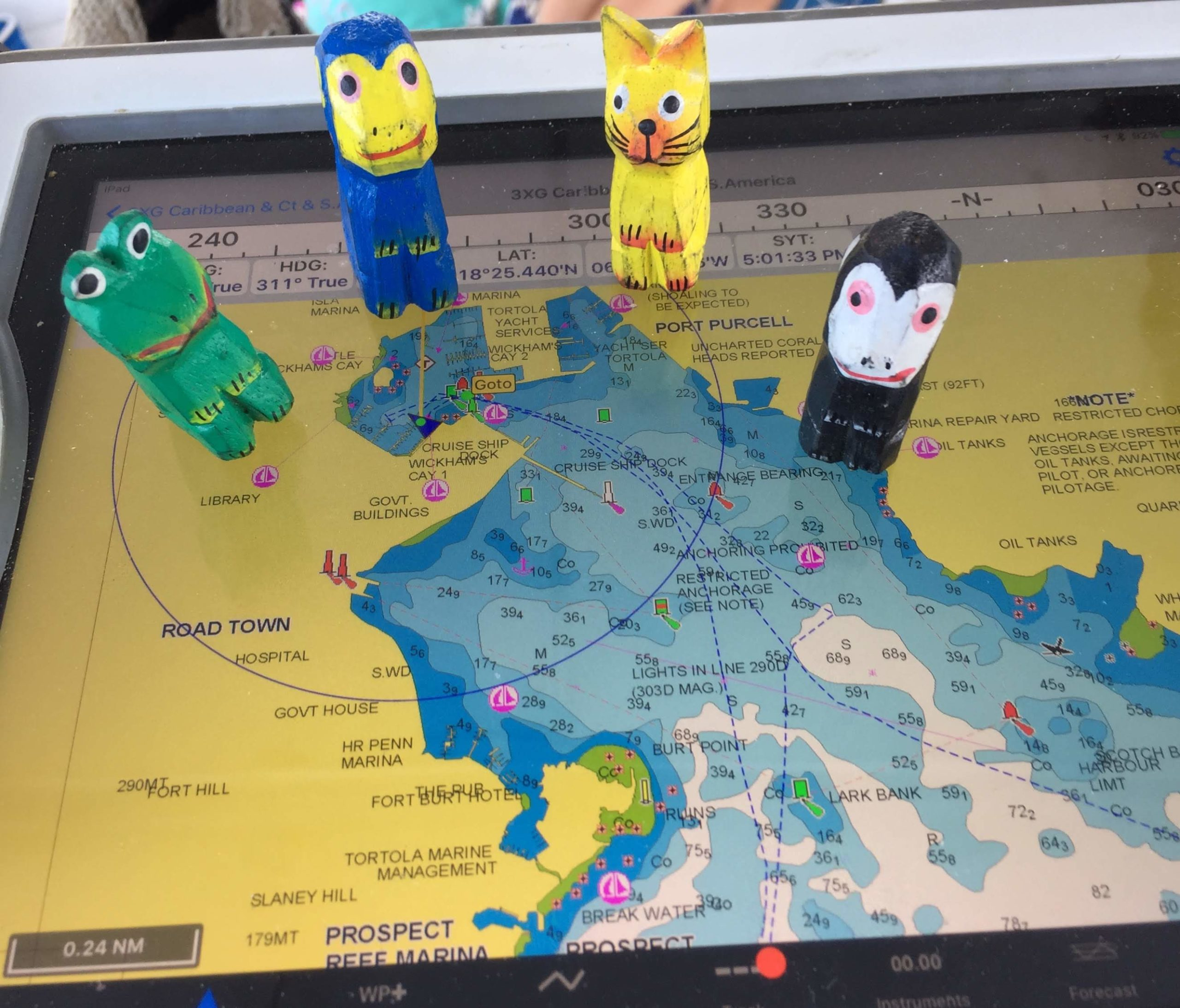 Four small figurines are on an electronic chartplotter as they learn to sail a sailboat.