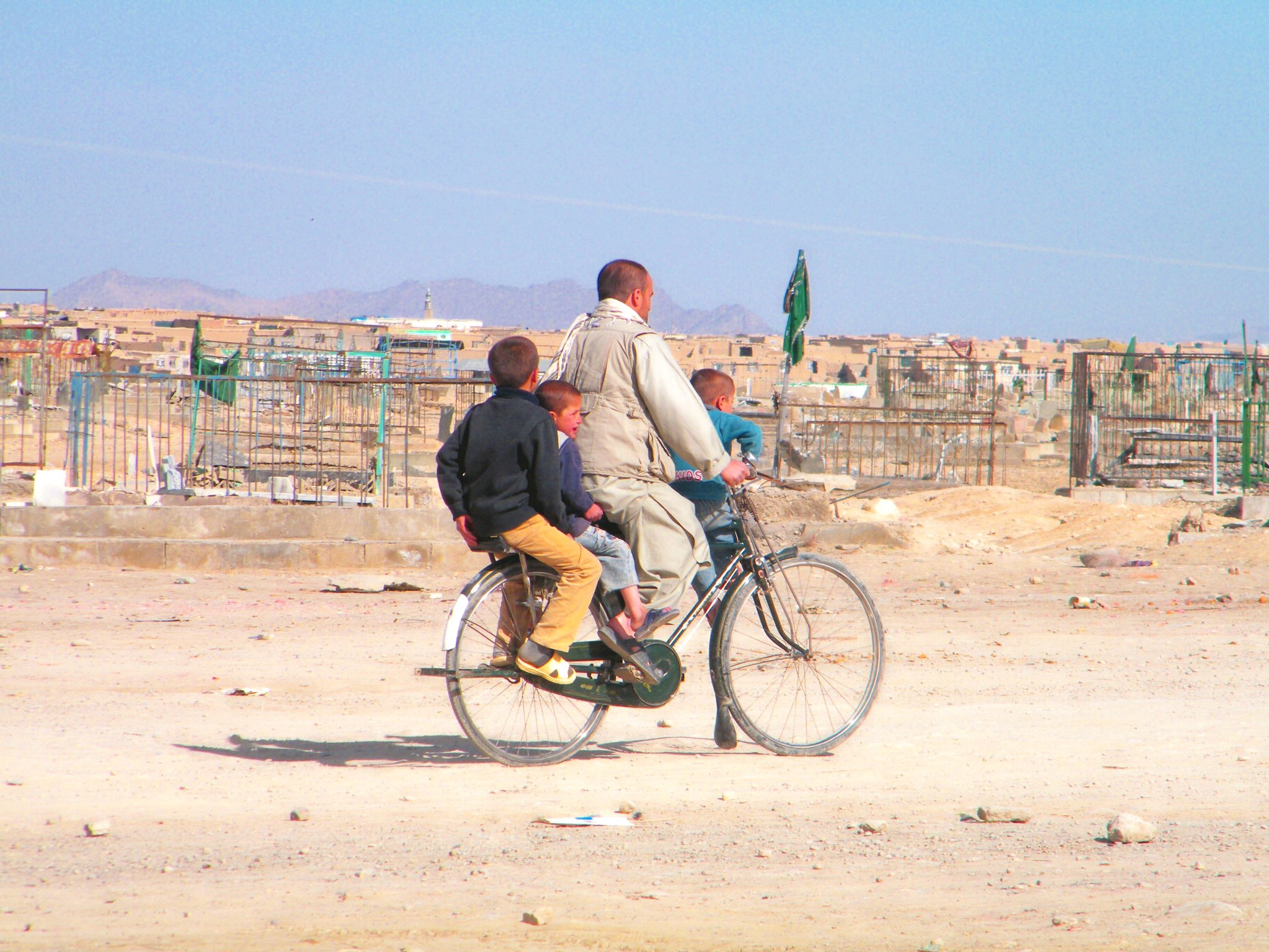 A father and three kids all ride a bicycle together in Afghanistan.