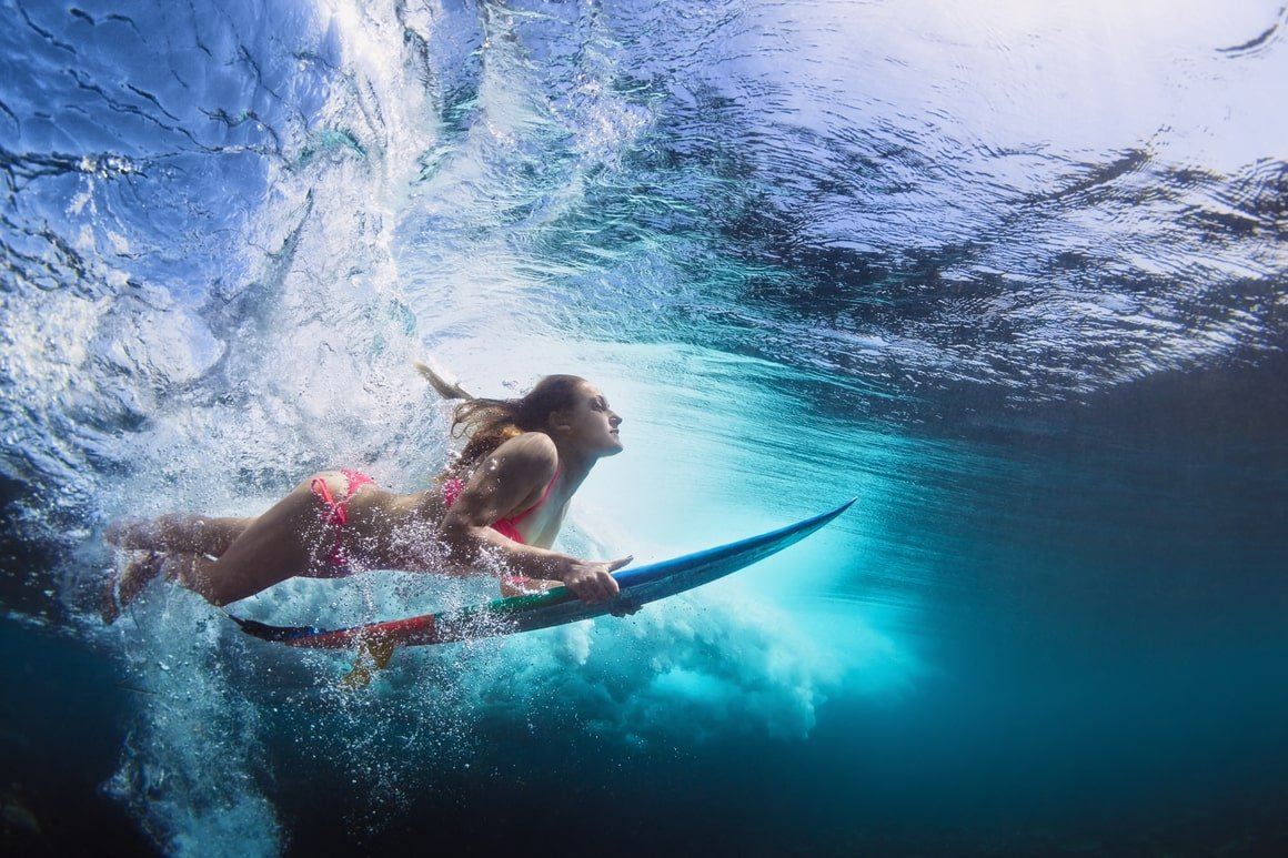 A girl ducks dives under a wave in French Polynesia