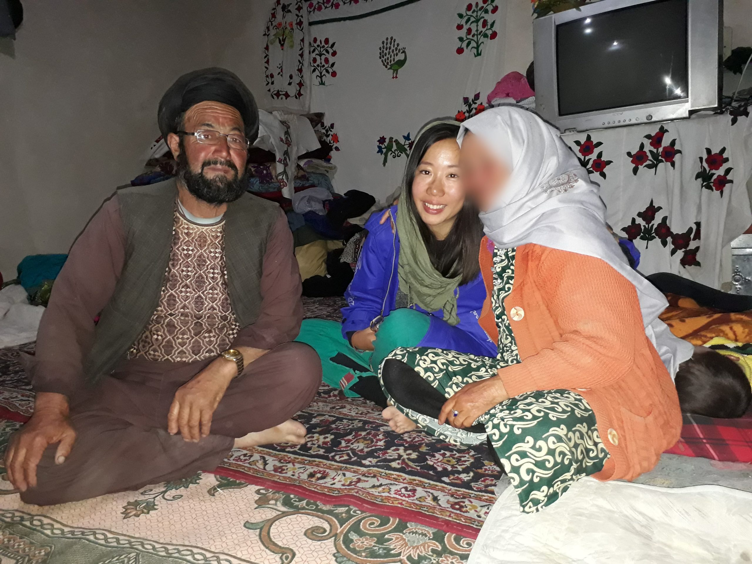 Marsha sits between her Afghani hosts. The woman's face is blurred out to respect her privacy.
