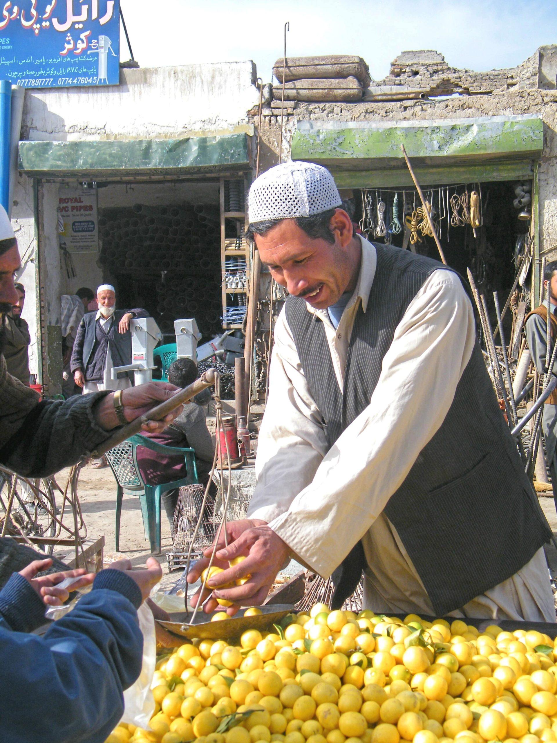 An Afgahni man weighs lemons.