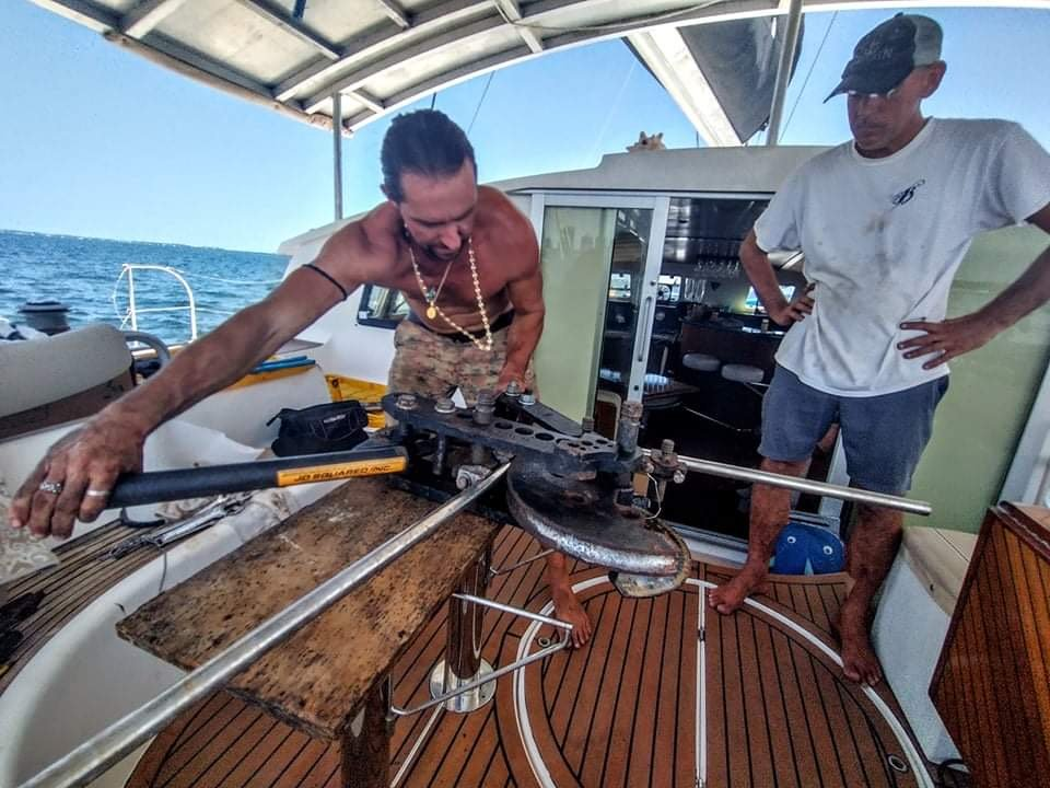 A man repairs something on his liveaboard sailboat.