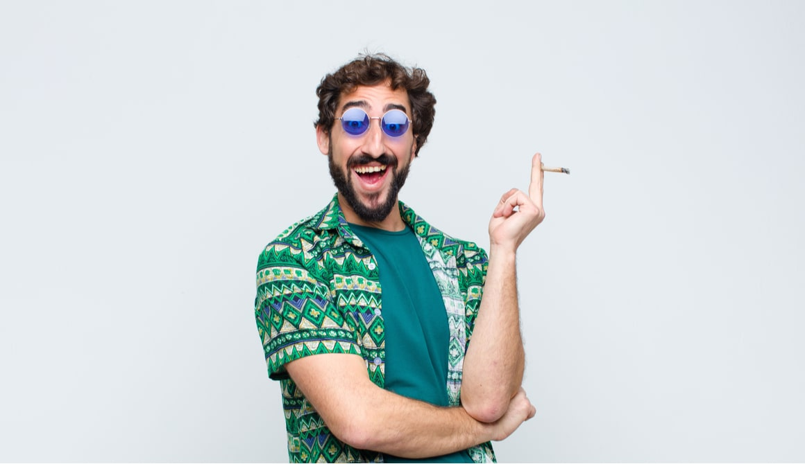 A guy with blue glasses holds a joint