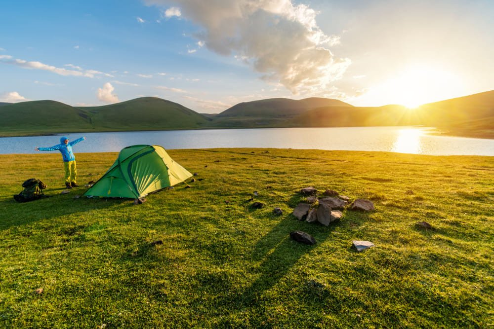 girl next to a tent and lake at sunrise