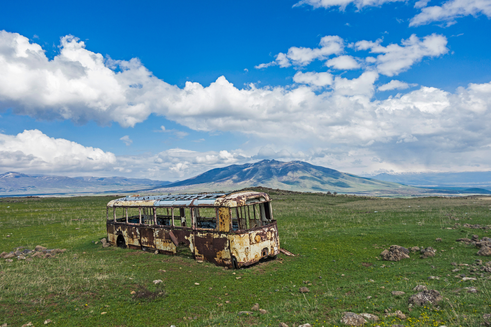 Abandoned old bus in a field of Armenia with a mountain in background