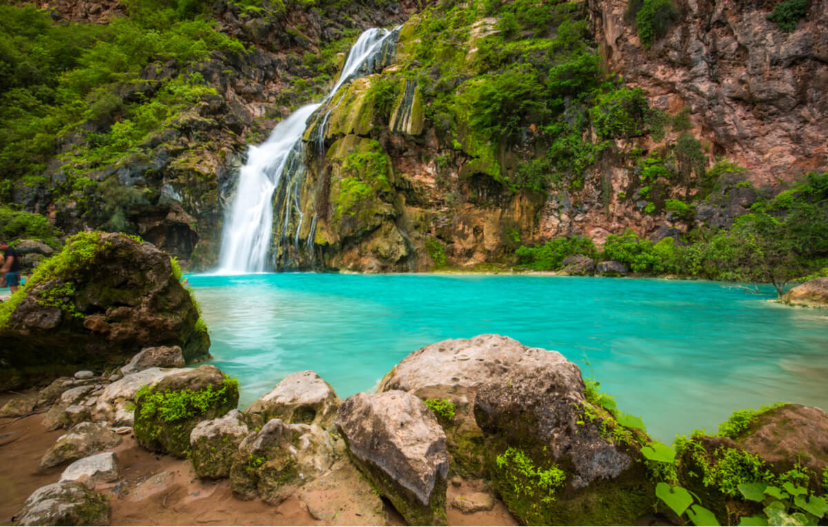 bright blue waterfall seen while backpacking oman