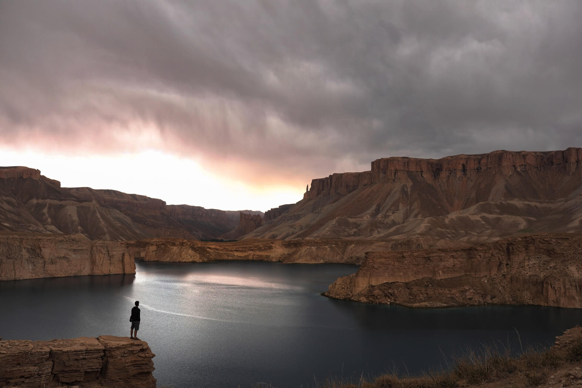 A backpacker in Afghanistan gazes out over a lake in Band-e-Amir National Park.