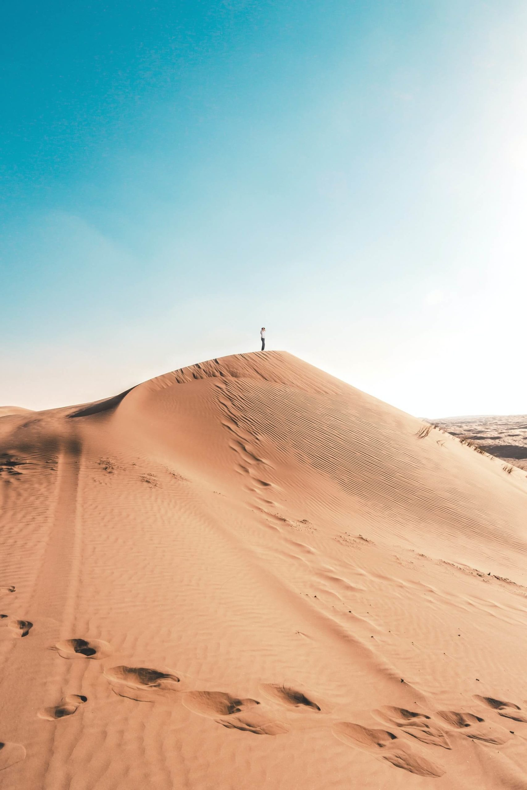 A backpacker in Oman summits a dune in the Sharqiyah Sands