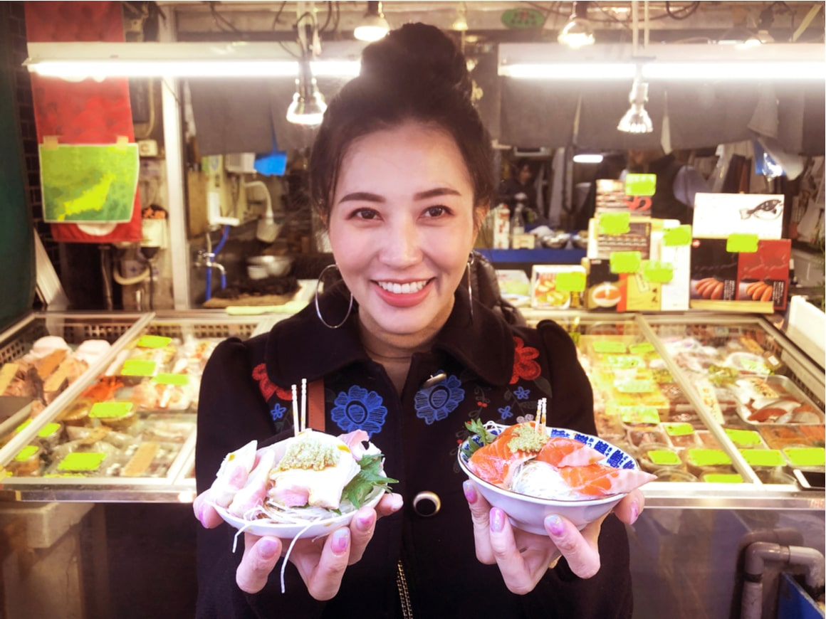 A woman holds two plates of street food in Japan.