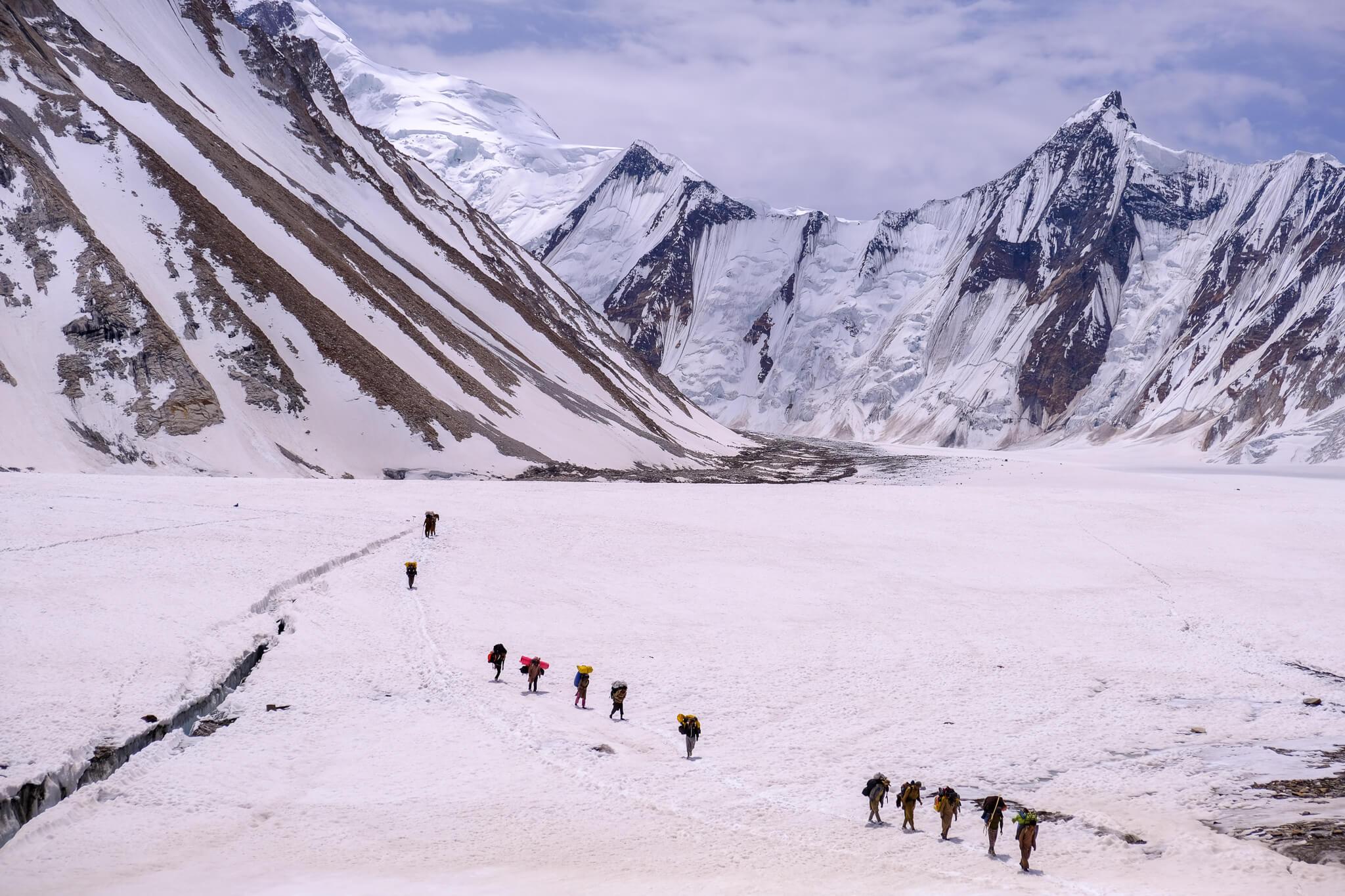 trekkers walking on white snow in Pakistan