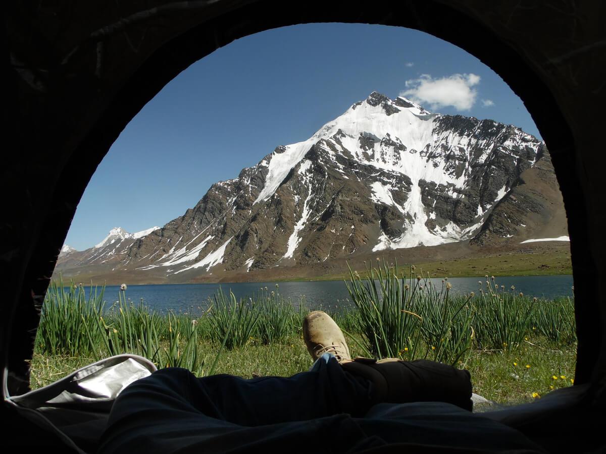 feeet poking out of a tent at karambar lake hiking in pakistan