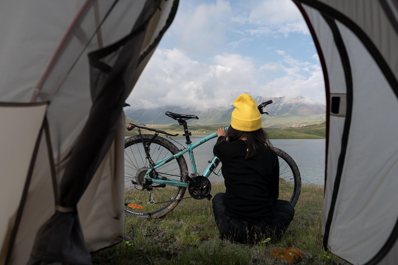Marsha Jean and her bike in front of a beautiful lake in Central Asia.