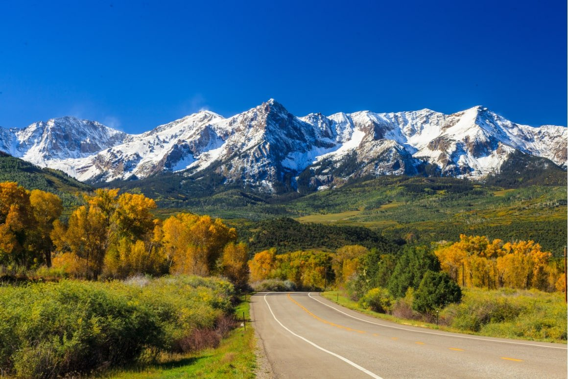 Snow capped mountains and autumn trees are in the distance. A straight road with no cars on it is in the foreground.