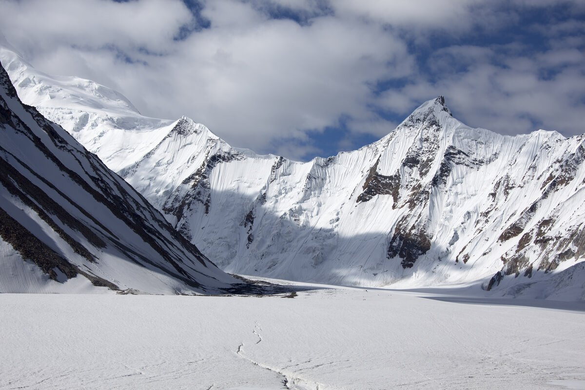 massive white mountains towering over a sea of snow in pakistan
