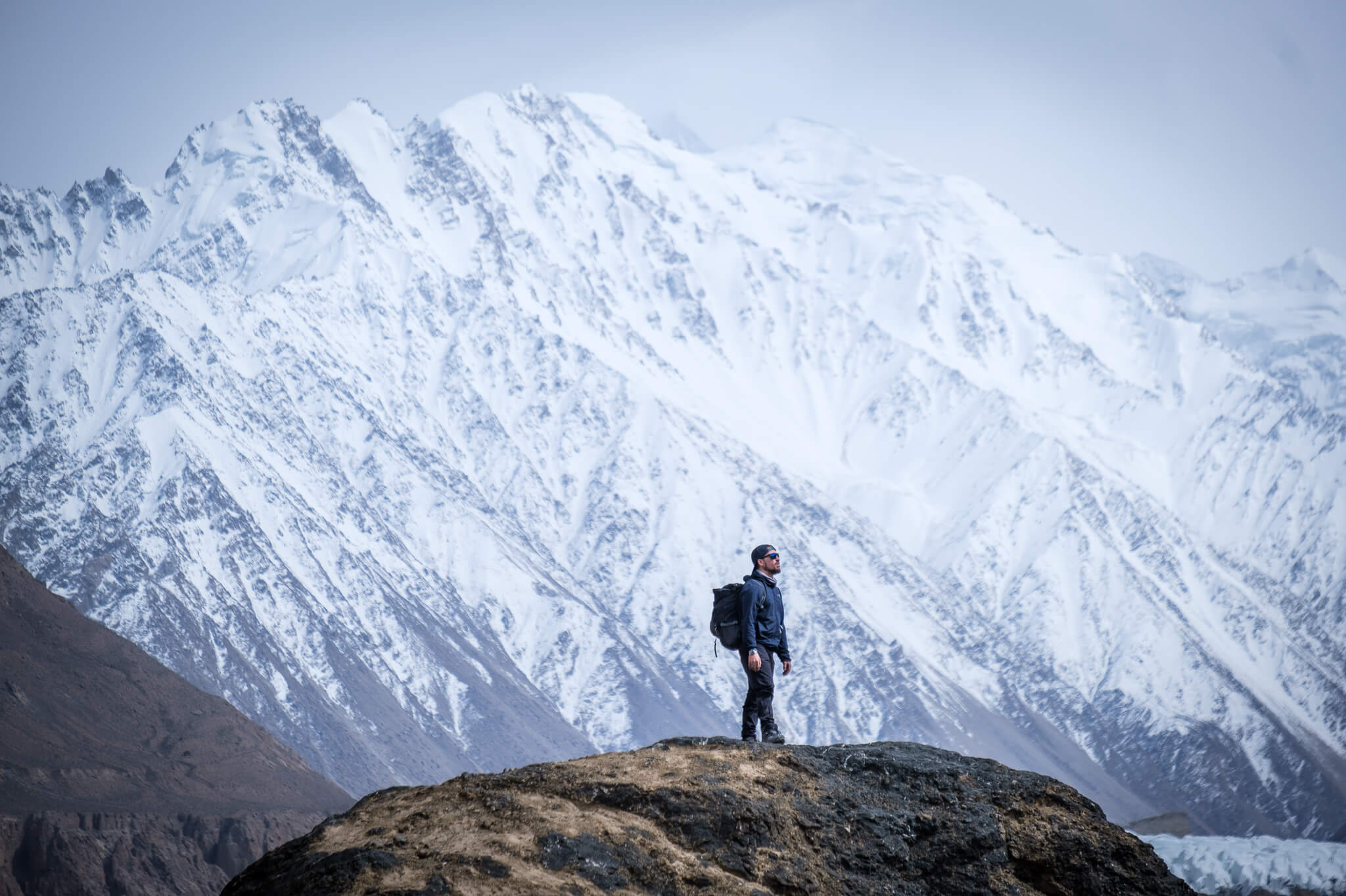 guy standing underneath snow capped mountain