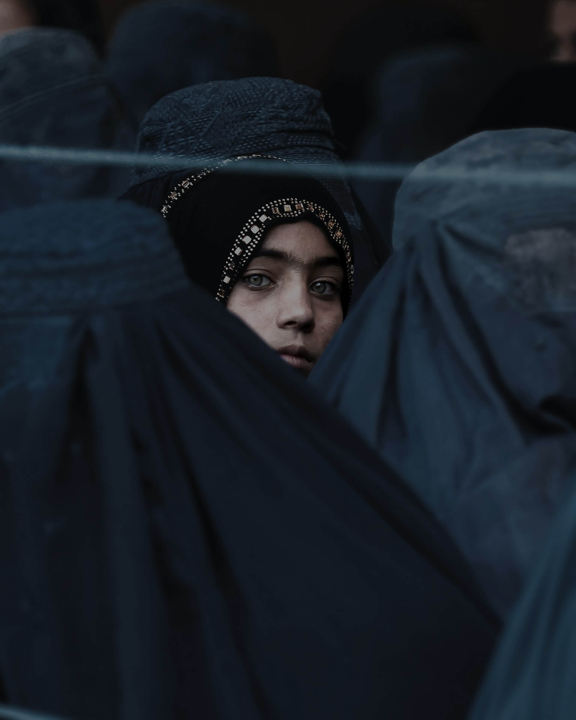 A young Afghan girl with blue eyes in a crowd of locals wearing burqas.