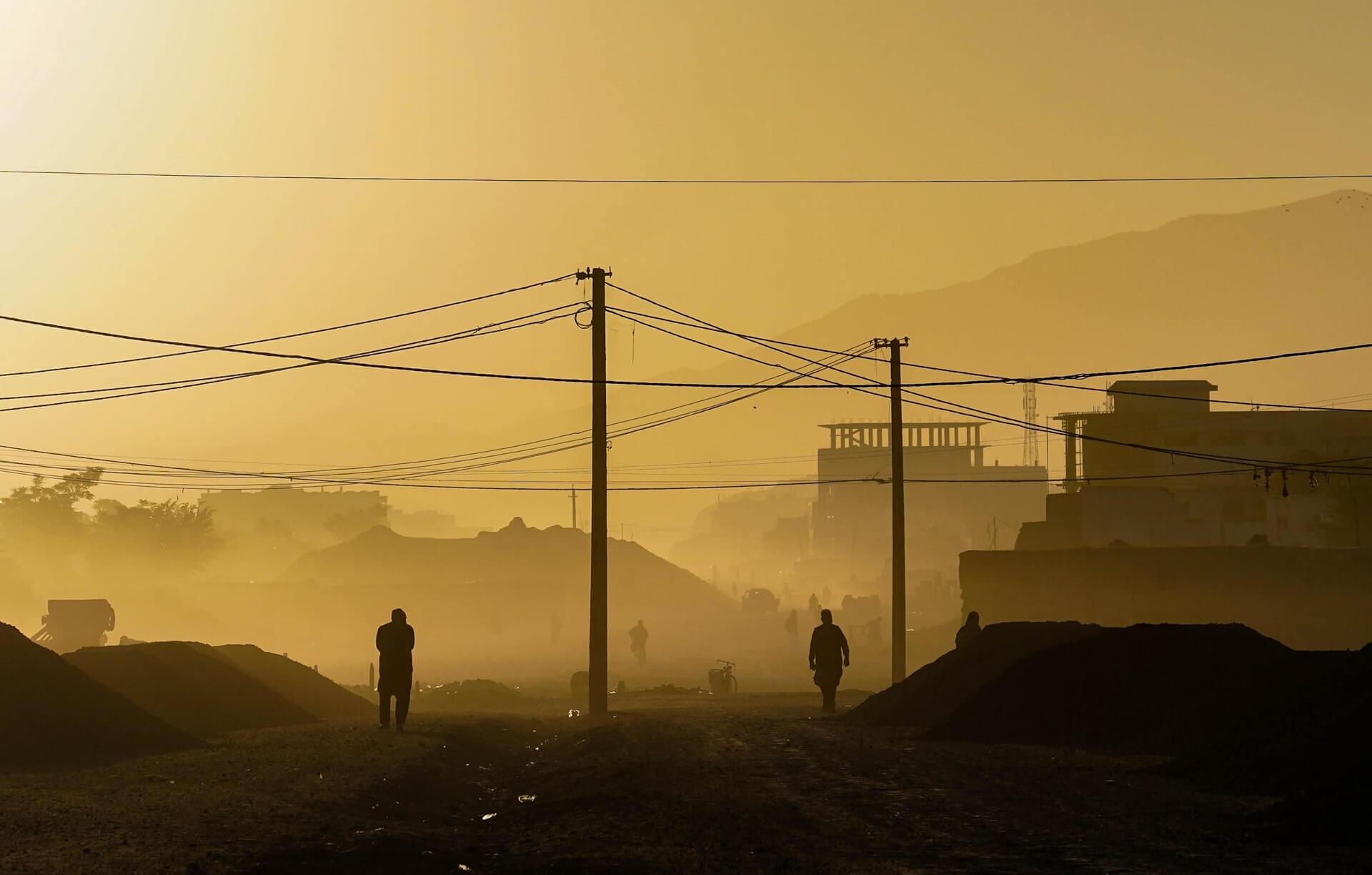 Locals walk down a dusty, desolate street in Kabul at sunrise.