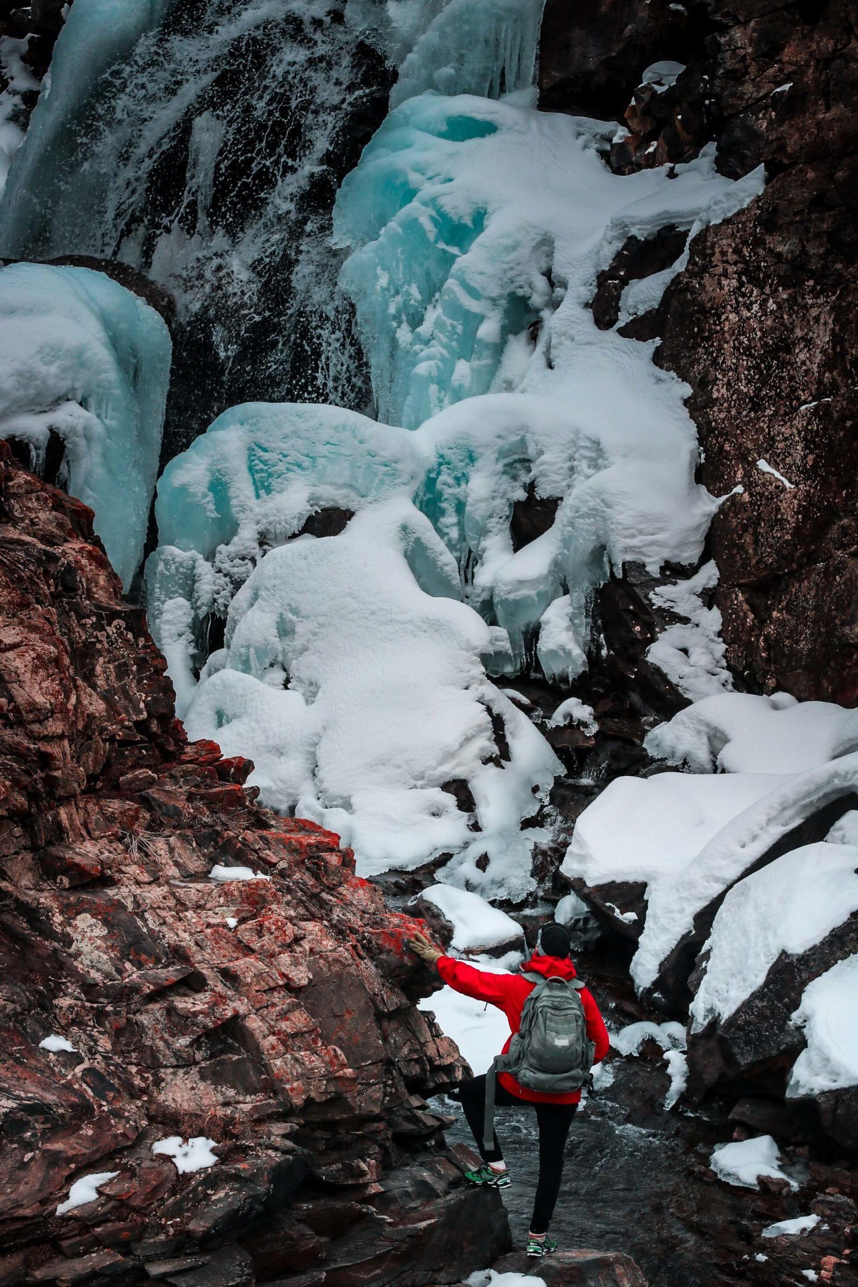 A trekker in Afghanistan stands underneath an ice drift in Panjshir.
