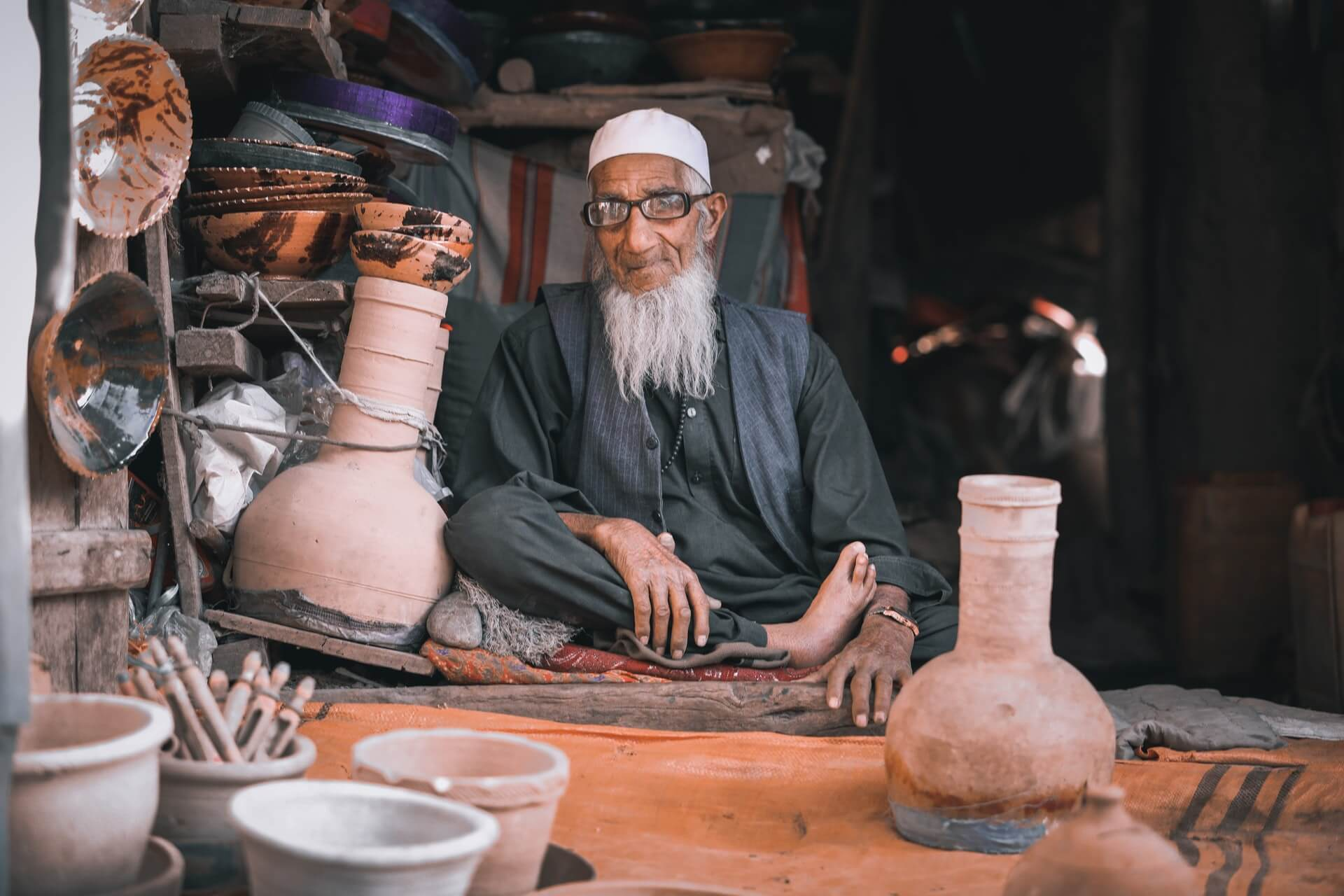 An old man selling clayware at a market in Parwan, Afghanistan.