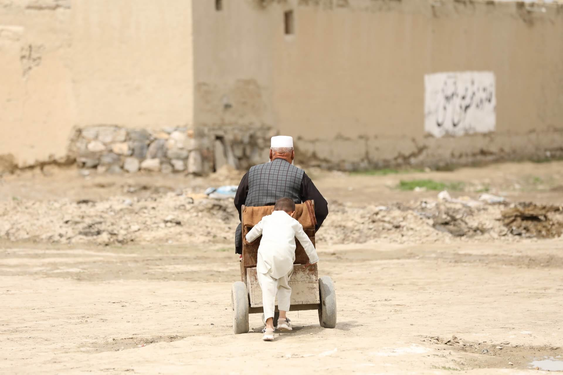 A small Afghan boy pushes his grandfather down a dusty road in a cart.