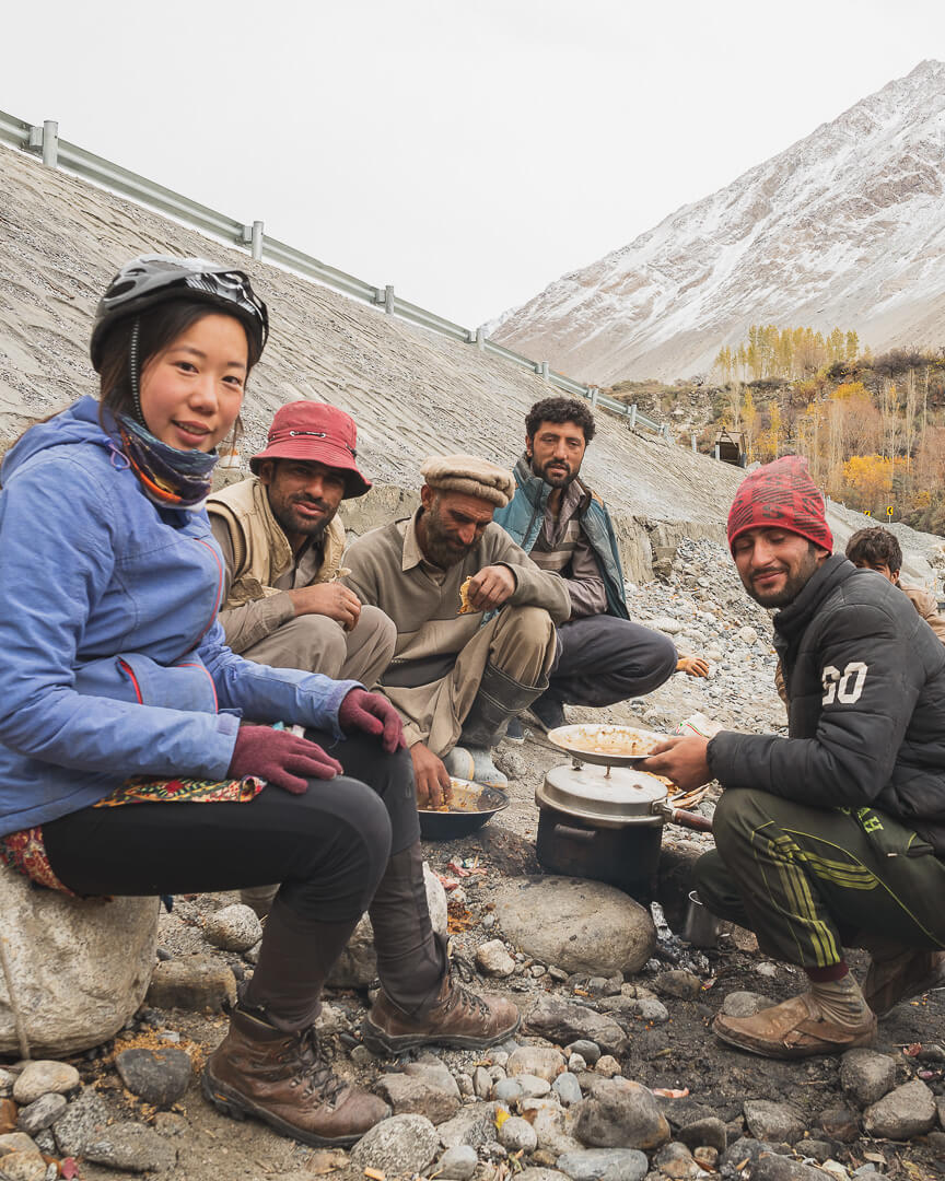 Marsha enjoys a roadside lunch with some locals during her bike tour in Pakistan.