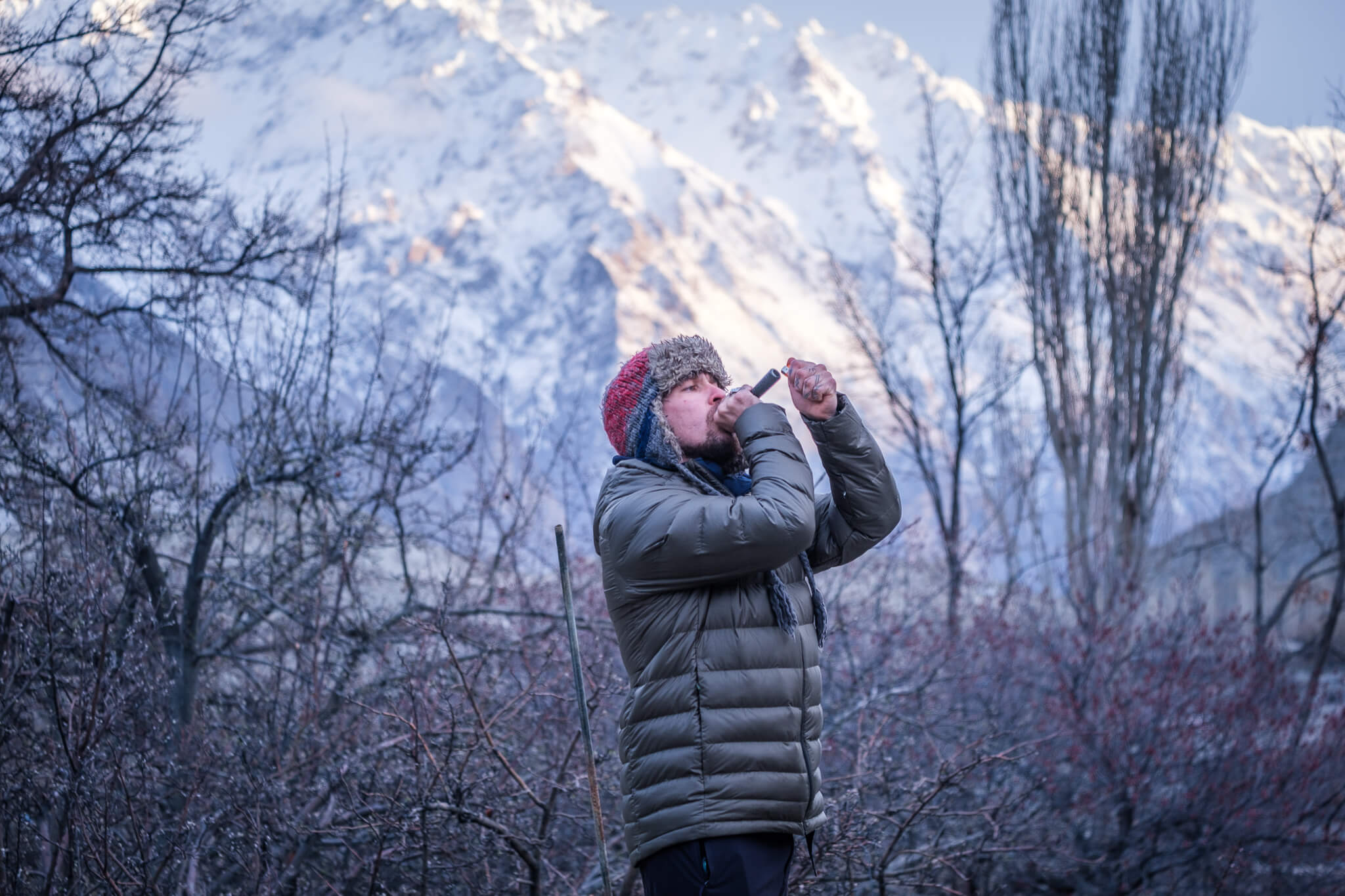 man smoking out of a chillum with a snow capped mountain in the background