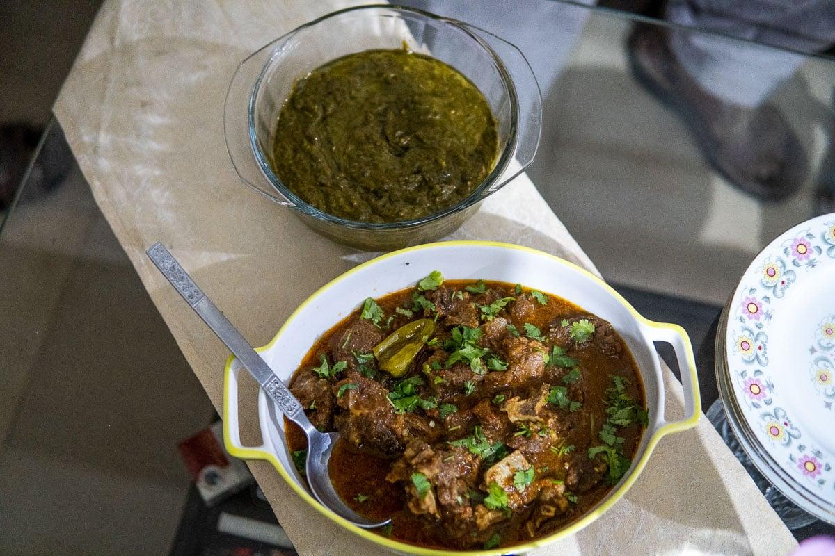 bowl of pakistani karahi and green saag paneer on a glass table