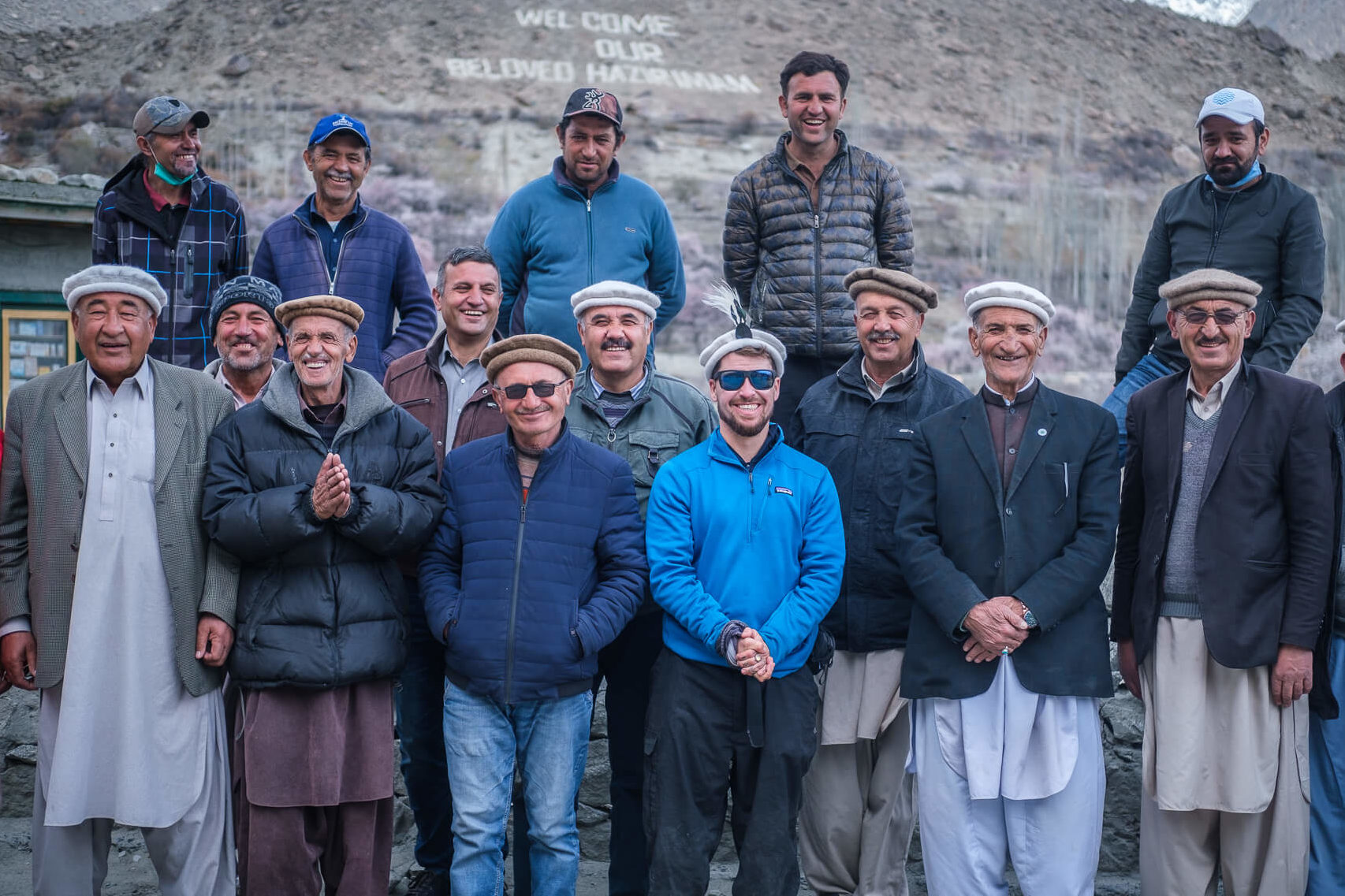 man standing with locals in hunza pakistan reasons to travel to pakistan